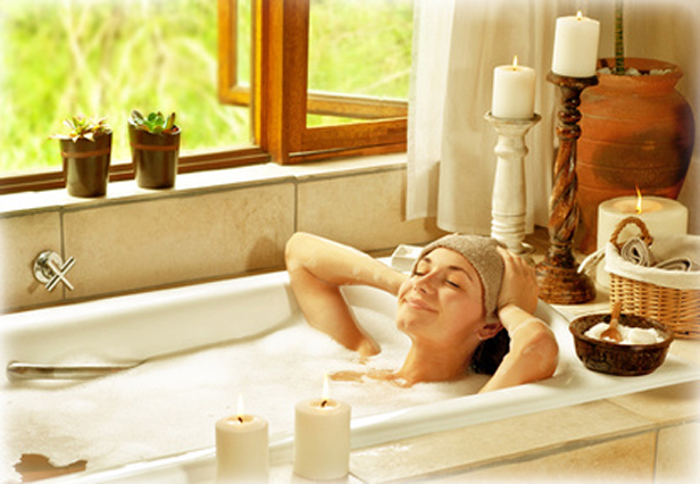 Woman taking bath, happy female relaxing at spa resort, young healthy girl at vacation, lady lying down in hot water, travel to luxury spa